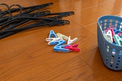 Colorful clothes pins and black hangers on the wooden flooring