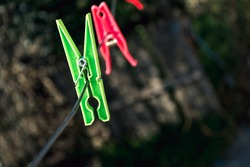 Colorful clothespins on the hangers. Plastic clothespins in different colors with bokeh background.
