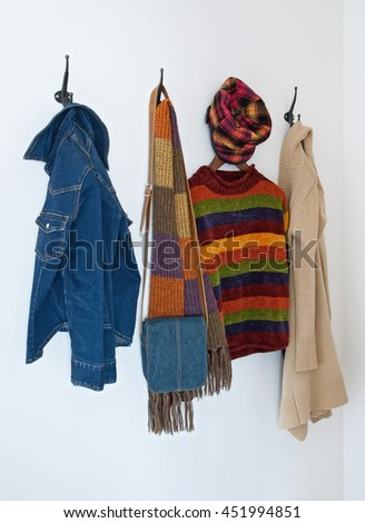 Colorful clothing and bag on metal coat hooks, on a white wall. Foto d'archivio ©