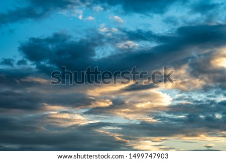 Colorful cloudy sky after rain, Beautiful evening skyscape. Sun's rays shine through hole in black clouds after rain. Sky, Golden sky. Natural background. Inspirational concept. #1499747903