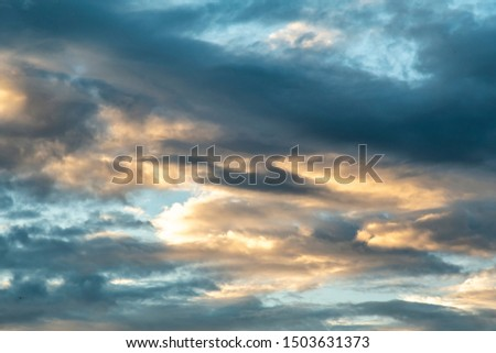 Colorful cloudy sky after rain, Beautiful evening skyscape. Sun's rays shine through hole in black clouds after rain. Sky, Golden sky. Natural background. Inspirational concept. #1503631373