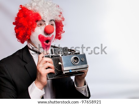 colorful clown with an instant camera on a white background