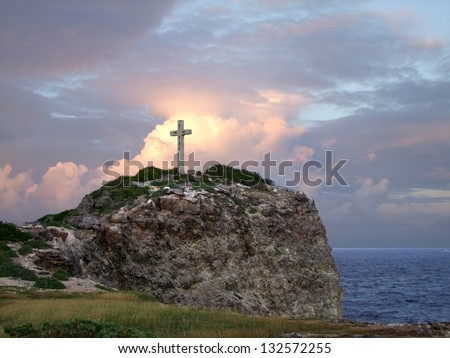 colorful coastal sundown scenery on a caribbean island named Guadeloupe including a summit cross on mountain top