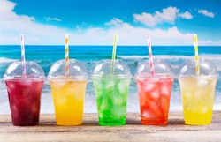 colorful cold drinks in plastic cups with ice on the beach.
