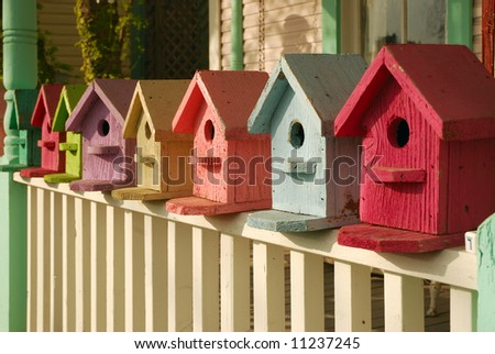 Colorful collection of birdhouses lined-up on a porch railing. - stock photo