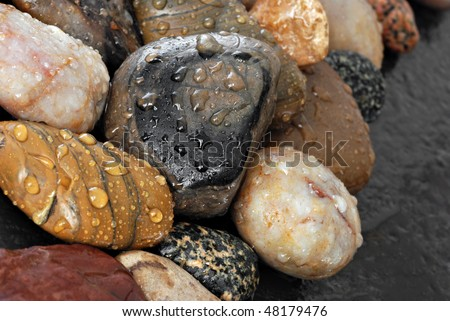 Colorful collection of small river stones with water droplets.  Macro with shallow dof.