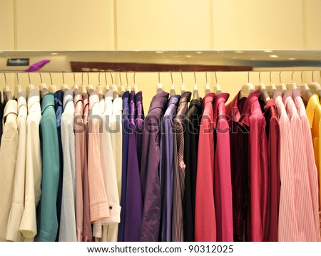 Colorful collection of women's clothes hanging on a rack.