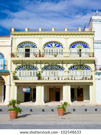 Colorful colonial building in Havana with  distinct traditional architecture elements such as porticoes,balconies and colorful stained glass windows and doors
