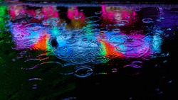 Colorful colors at night as a reflection in the water of a puddle at a folk festival