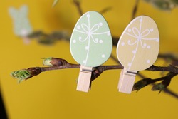 Colorful colourful Easter egg decoration on twigs with Catkin pussy willow on pastel yellow background.Bunch of pussy willow branches with catkins.Spring mood.Postcard Template.Easter composition.