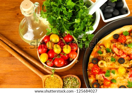 colorful composition of delicious pizza, vegetables and spices on wooden background close-up