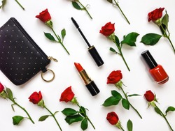 Colorful composition with red bright roses, purse and woman accessories. Flat lay on white table, top view