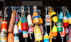 Colorful concrete anchors or buoys with ropes decoratively hanging on a metal bar