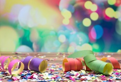 colorful confetti and streamer lying on floor in fron of background