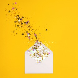 Colorful confetti pouring out of white envelope on yellow background. View from above. Flat lay. Holiday, congratulation or good news concept. Place for text.