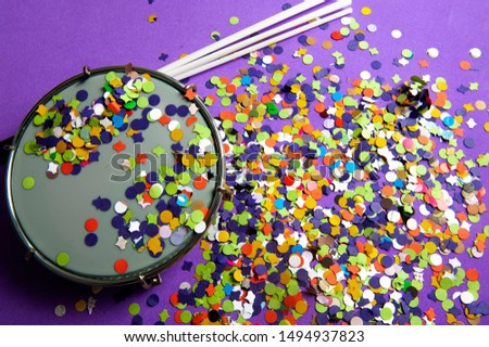 Colorful confetti, used in carnival.Tamborim instrument used in street blocks, parade school of samba.A lilac background.View from the top.