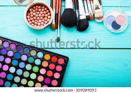 Colorful cosmetics on blue wooden workplace. Top view