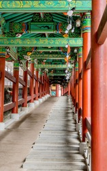 Colorful covered walkway with stairs and wheelchair ramp at Buddhist temple.