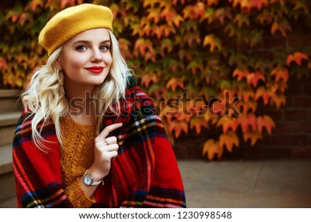Colorful, cozy autumn, fashion concept. Outdoor portrait of young beautiful happy smiling girl wearing yellow beret, wrist watch, sweater. Model wrapped in tartan blanket. Copy, empty space for text
