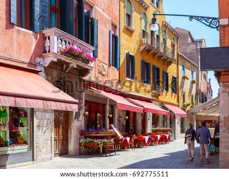 Colorful cozy street with tables of cafe at  a sunny morning, Venice, Italy