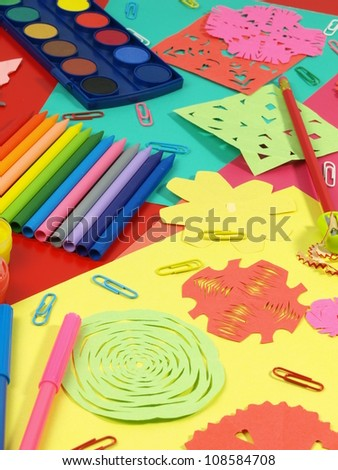 Colorful craft equipment on children's desk, paper-cut and crayons