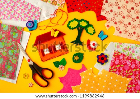 Colorful crafts made of felt. Crafts from colorful sheets of felt on a yellow background. The image of the house, tree, snails, butterflies and colors of felt. Cut, sew and glue the felt.