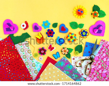 Colorful crafts made of felt. To make crafts from felt as a type of needlework and a hobby. Crafts from felt on a yellow background. There is space for text.