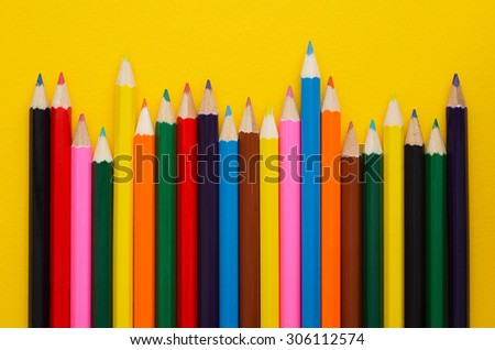 Colorful crayons organized in a row over yellow background, above view