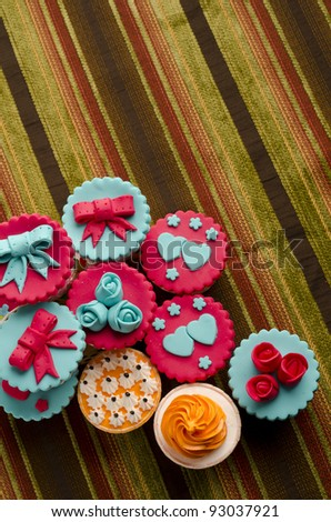 Colorful cup cakes isolated on cotton background
