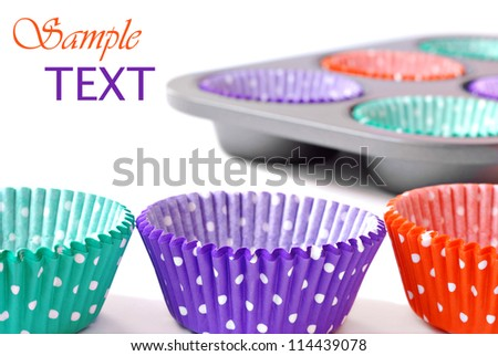 Colorful cupcake wrappers with baking pan on white background with copy space.  Macro with shallow dof.