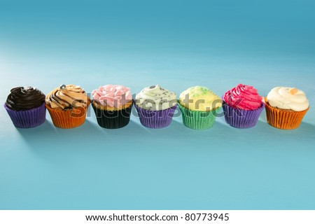 colorful cupcakes arrangement in a row on turquoise studio background
