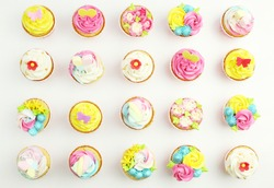 Colorful cupcakes on white background top view