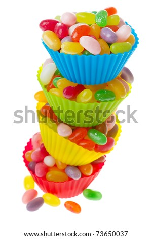 Colorful cups full with jelly beans isolated over white background