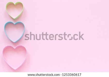 Colorful cutters cookies in heart shape on pastel pink background. Concept Valentine's card. Top view Copy space for text. #1253360617