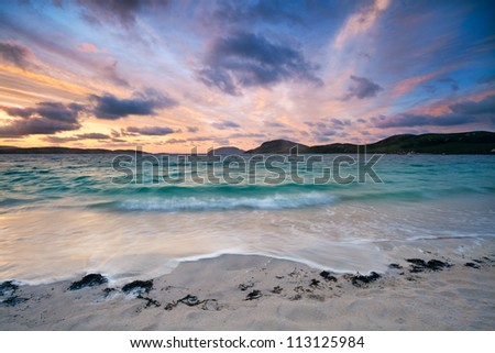Colorful dawn on a white sandy beach . Stunning sunrise over Vatersay beach, Outer Hebrides, Scotland .