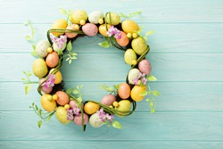 Colorful decorative Easter eggs wreath on light blue wooden background