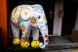 Colorful decorative statue of an elephant painted with Singapore map and oriental ornaments in front of the cafe in hip Haji Lane street in Kampong Glam, Singapore.