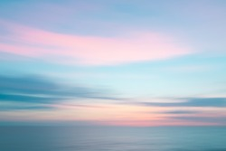 Colorful defocused sunset sky and ocean nature background with blurred panning motion.