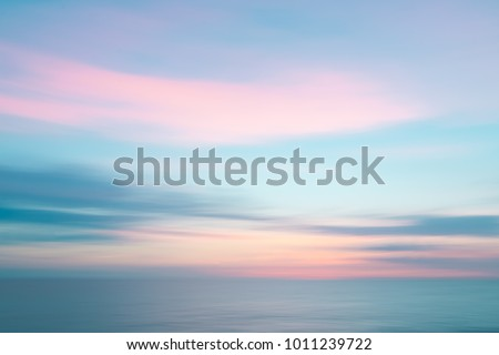 Colorful defocused sunset sky and ocean nature background with blurred panning motion. #1011239722