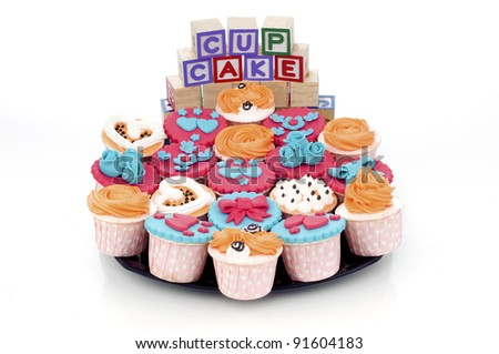 Colorful delicious cup cakes in black plate isolate white background with word cube stack on each others