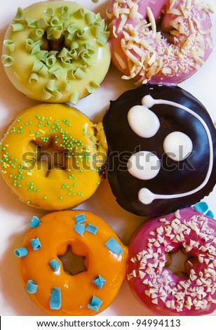 Colorful delicious donuts and one smiling cake isolated on white background