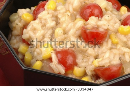Colorful delicious risotto served in a black bowl.