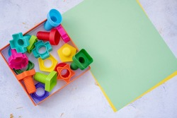 colorful details of the designer. Children's creativity and learning. Home leisure. educational constructor for children, nuts and bolts in the form of geometric shapes. empty space for your text.