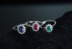 Colorful diamond rings. Rings with sapphire, ruby, emerald diamonds. On a background.
