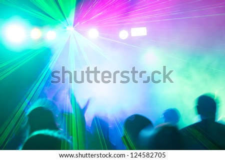 Colorful disco laser lights illuminating crowd at party.