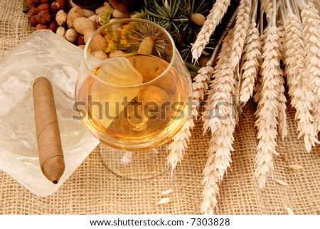 Colorful display of harvest nuts on burlap cloth, jute. Glass of brandy, cognac and ashtray with cigar on the side