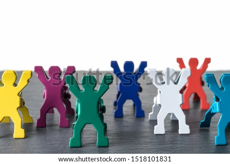 Colorful diverse miniature people figurines standing in a row on a dark stone slate plate. Isolated on white background. Diversity abstract concept.