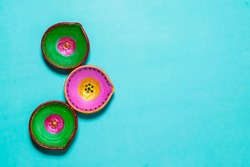 Colorful Diwali diyas with a blue background. Diwali Diya is a small lamp that is lit especially at Diwali. Diyas are typically made of clay with Ghee or oil used as the fuel and cotton wool as a wick
