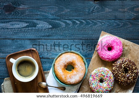Colorful Donuts and coffee breakfast composition with different color styles of doughnuts over an aged wooden desk background. #496819669