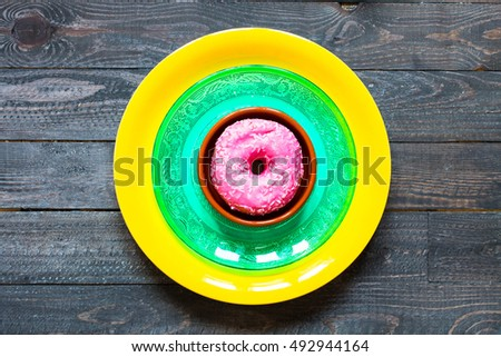 Colorful Donuts breakfast composition with different color styles of doughnuts over an aged wooden desk background. #492944164